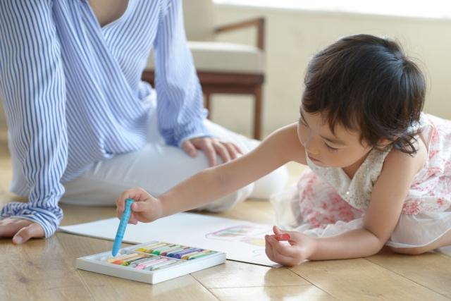 母親のそばで絵を描く子ども